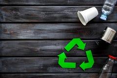 Wiederverwertung des Symbols mit Schale, Plastikflasche, Dose für Ökologie auf hölzernem copyspace Draufsicht des Hintergrundes stockfoto
