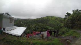 Wiejscy domy i założenia budujący wzdłuż wąskiej cewienie zygzag drogi przy stroną górzyste Cordillera falezy zdjęcie wideo