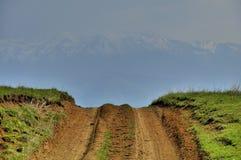 Wiejska droga krajobraz z ścieżką krzyżuje wzgórza Zdjęcie Royalty Free