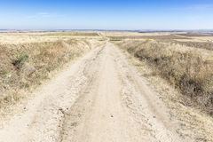 Wiejska droga na letnim dniu i niebieskim niebie Zdjęcia Stock