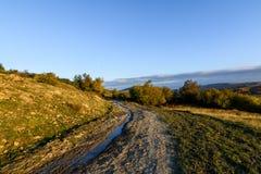 Wiejska droga w jesień krajobrazie Halna wiejska droga z wodą a Obraz Royalty Free