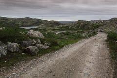 Wiejska droga wśród zielonych wzgórzy i jezior na chmurnym dniu Obrazy Stock