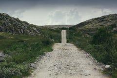 Wiejska droga wśród zielonych wzgórzy i jezior na chmurnym dniu Fotografia Stock