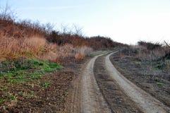 Wiejska wiejska droga w wczesnej wiośnie Ślad od samochodów pole Obraz Stock