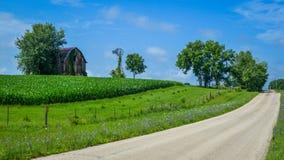 Wiejska Droga z stajnią, wiatraczkiem i kukurudzą, fotografia stock