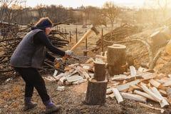 Wiejska kobieta strzela popiółu drzewa drewno dla zbierać dla zimy z ax obraz royalty free