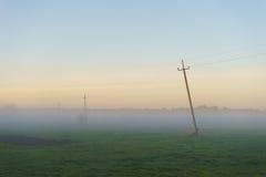 Wiejska sceneria z starą linią energetyczną w gęstej mgły ranku Obraz Stock