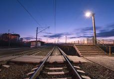 Wiejska stacja kolejowa przy nocą z niebieskim niebem linia kolejowa Obrazy Stock