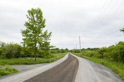 Wiejska żwir wiejska droga na chmurnym dnia krajobrazie Zdjęcia Stock