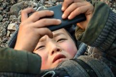 Wiejski ściółki chłopiec nałogowiec bawić się telefon komórkowego zdjęcia stock