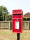 Wiejski czerwony królewski skrzynka pocztowa wieśniak na zewnątrz ulicznej wioski Fotografia Stock