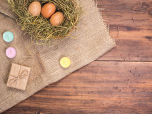 Wiejski eco tło z brown kurczaków jajkami, barwionymi świeczkami, prezenta pudełkiem i słomą na tle stare drewniane deski, Fotografia Stock