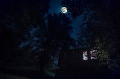 Wiejski gothic kasztel z rozjarzonymi okno w ciemnym lesie przy nocnym niebem z księżyc Obrazy Royalty Free