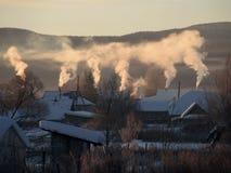 Wiejski krajobraz z dymienie kominami Obrazy Stock
