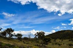 Wiejski krajobraz z górami i chmurzącym niebieskim niebem obraz royalty free