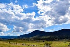 Wiejski krajobraz z górami i chmurzącym niebieskim niebem zdjęcia stock