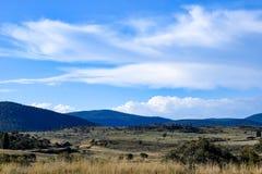 Wiejski krajobraz z górami i chmurzącym niebieskim niebem fotografia stock