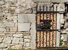 Wiejskie dekoracje Czarny dokonanego żelaza drzwiowy przymknięcie drewniany magazyn z kwiatu garnkiem w środku na kamiennej budyn Zdjęcie Stock