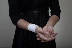 Wiek średni kobieta pokazuje jej bandażującego nadgarstek Fotografia Stock