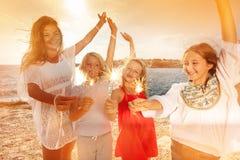 Wiek dojrzewania ma zabawę używać sparklers na plaży przyjęciu zdjęcie royalty free