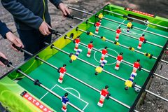 Wiek dojrzewania sztuki sto?u futbol w ulicie Gra sto?owy futbol M?odzi ludzie bawi? si? gr? planszow? outdoors w lecie zdjęcie stock