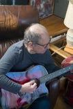 Wieka średniego starszy mężczyzna bawić się gitarę fotografia stock