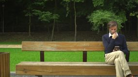 Wieka średniego mężczyzna obsiadanie na ławce, use smartphone, opowiadający i odpoczynek w parku zdjęcie wideo