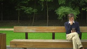 Wieka średniego mężczyzna z brody obsiadaniem na ławce, use smartphone i odpoczynek w parku zbiory wideo