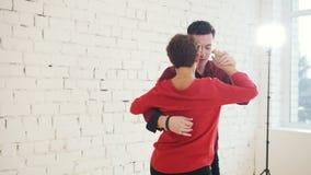 Wieka średniego młody człowiek w czerwonej koszula i kobieta jesteśmy dancingowym kizomba w studiu zdjęcie wideo