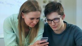 Wieki dojrzewania czyta niektóre zawartość w smartphone który robi one ono uśmiechać się zbiory wideo