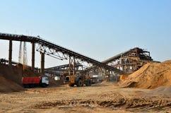 Wiel front-end lader het leegmaken zand in zware stortplaatsvrachtwagen Verpletterend fabriek, machines en materiaal om te verple stock foto