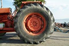Wiel van oude, oranje tractor stock afbeeldingen