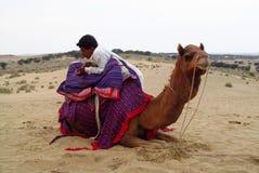 Wielbłąd z mężczyzna lying on the beach na piasku w pustyni Obrazy Royalty Free