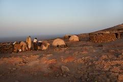 Wielbłądy i ludzie w afrykanin pustyni blisko glinianych budynków są małym oazą zmierzch barwią everything w menchiach, Etiopia Fotografia Royalty Free