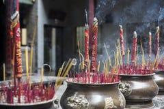 Wielcy czerwieni kadzidła kije z Chińskimi charakterami na one w brązie puszkują w Buddyjskiej świątyni w Ho Chi Minh mieście zdjęcie royalty free