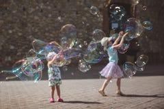Wielcy mydlani bąble latają w powietrzu outside Dzieci bawić się w tle w letnim dniu obrazy stock