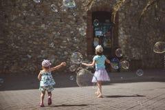 Wielcy mydlani b?ble lataj? w powietrzu outside Dzieci bawi? si? w tle w letnim dniu fotografia royalty free