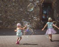 Wielcy mydlani b?ble lataj? w powietrzu outside Dzieci bawi? si? w tle w letnim dniu obraz royalty free