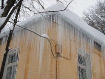 Wielcy niebezpieczni sople wiesza od dachu żółty budynek obrazy royalty free