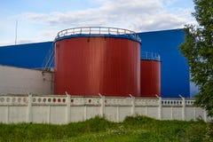 Wielcy przemysłowi zbiorniki czerwony kolor przeciw błękitnemu przemysłowemu budynkowi fotografia stock