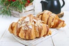 Wielcy smakowici croissants z migdałowymi płatkami na białym drewnianym tle Francuscy ciasta Zdjęcia Royalty Free