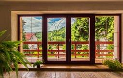 Wielcy szklani drzwi w domu nad którym otwiera panorama góry pod niebieskim niebem obrazy stock