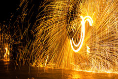 Wielding a light show. The beach blazes on the beach at night Stock Image