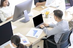 Wiele Azjatyccy pracownicy są uważnie na pracować z nowożytnymi komputerami fotografia stock