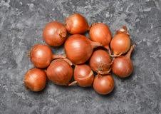 Wiele cebule na szarej betonowej powierzchni pożytecznie warzywa obraz stock