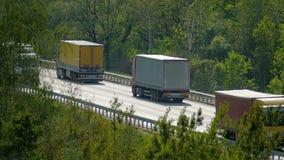 Wiele ciężarówek i samochodów jeżdżenie na autostradzie wśród drzew zdjęcie wideo