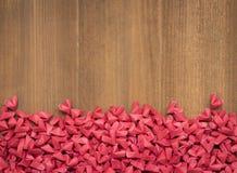 Wiele czerwoni mali papierowi serca kształtowali na drewnianym tle Obrazy Royalty Free