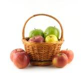 Wiele dojrzali kolorów jabłka w brown łozinowym koszu i zbliżają je odizolowywający zbliżenie Obrazy Stock