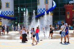 Wiele dzieci sztuka na boisku z fontannami w gorącym lecie Zdjęcie Royalty Free