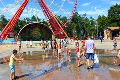 Wiele dzieci sztuka na boisku z fontannami w gorącym lecie Fotografia Royalty Free